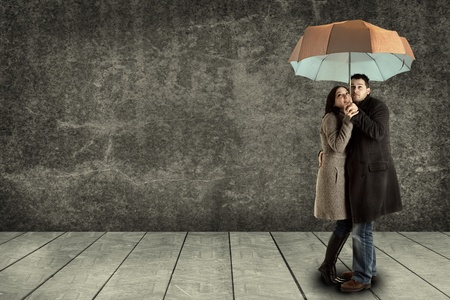 young couple searching protection under an umbrella photo
