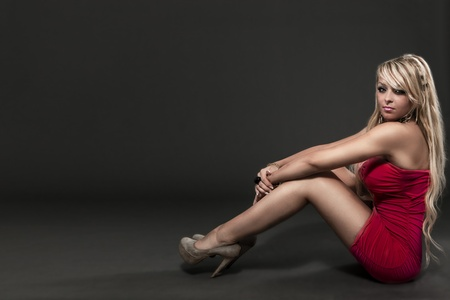 photo of amazing blonde woman with red cocktail dress over grey background  photo