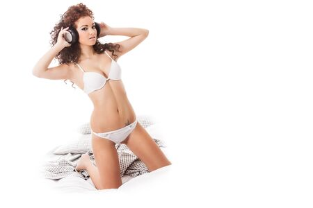 Stockphote, Curly woman with white lingerie and headphones in the bed photo