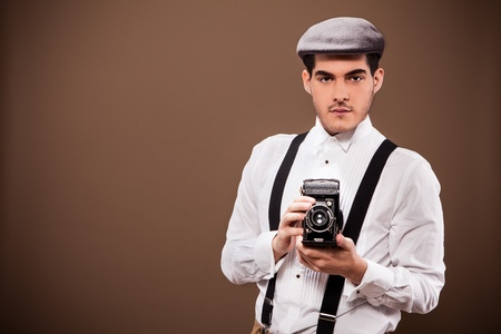 Photo of cute guy with old dslr camera and old outfit from the 30s photo