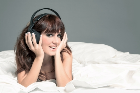 Stockphoto, smiling woman in lingerie and headphones on the bed photo