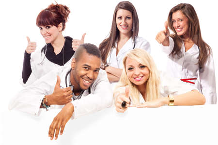 Young medical students smiling making positive thumb gesture in front of a message board photo