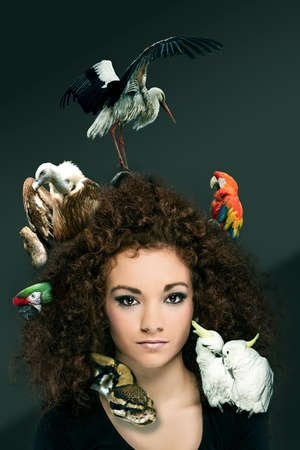 photo of beautiful curly woman with different animals in her hairs, zoo concept, photo