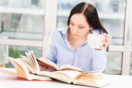 Photo Female Student learning at home with different books photo