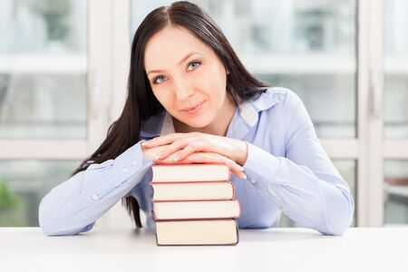 photo of pretty student smiling over book pile photo