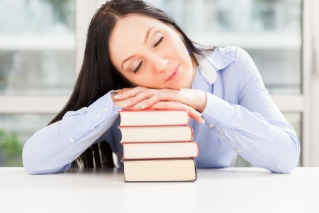 photo of pretty student sleeping on book pile photo
