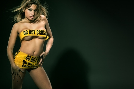 Fashion image of sexy woman wrapped in yellow crime scene tape