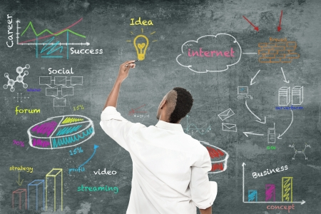 african business: photo of afro amercian man drawing a strategy diagram on the wall Stock Photo
