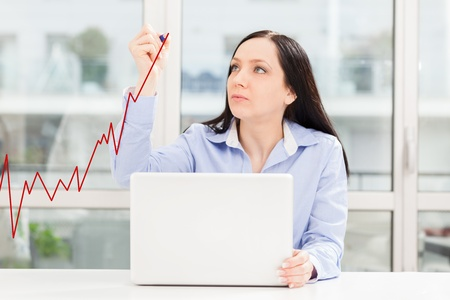 increase diagram: woman is drawing positive business growth with a red pen