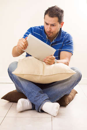 young adult man: photo of young adult man playing with tablet pc at home