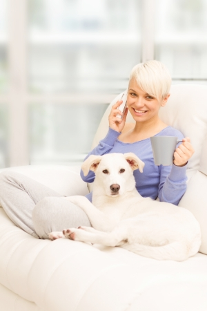 Photo of woman with the dog on the sofa holding a mug and phoning photo