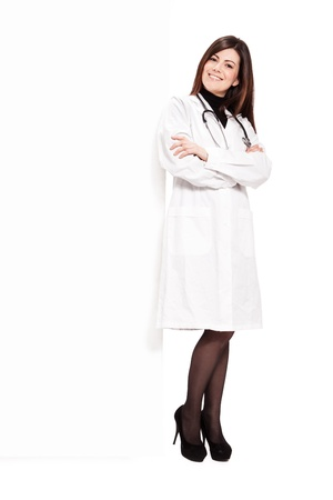 Photo of brunette doctor with white messageboard - isolated Stock Photo - 19563167