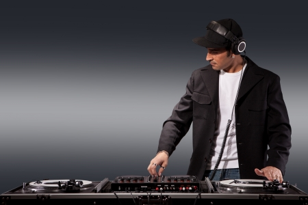 Photo of adult dj working with his equipment photo