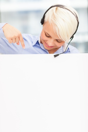female support assistant is smiling while indicating a banner with her finger Stock Photo - 20151204