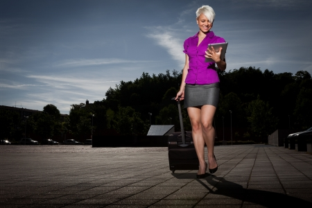 trolley: photo of attractive Businesswoman with trolley and tablet pc walking  Stock Photo