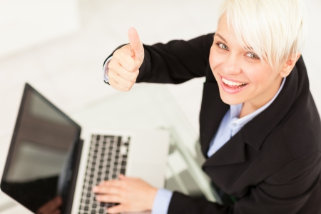 Businesswoman making positive thumb gesture while smiling in the office photo