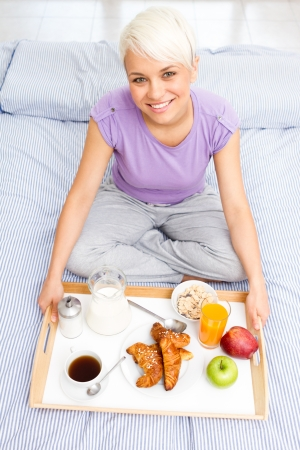 Young blonde woman is having breakfast in the bedroom photo