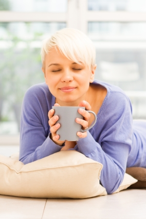 woman drinking tea: Photo of pretty woman with mug on the floor laying on a pillow