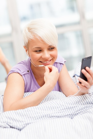 conversating: young woman phoning in the bed with headphones Stock Photo