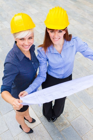 female constructors holding the project in the hands while smiling Stock Photo - 20546802