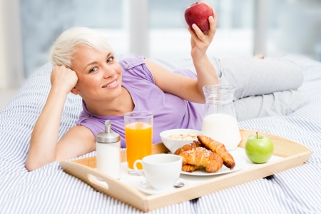Young blonde woman is having breakfast in the bedroom