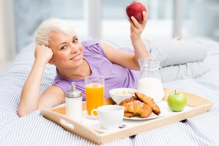 若いブロンドの女性は、寝室で朝食を持っています。