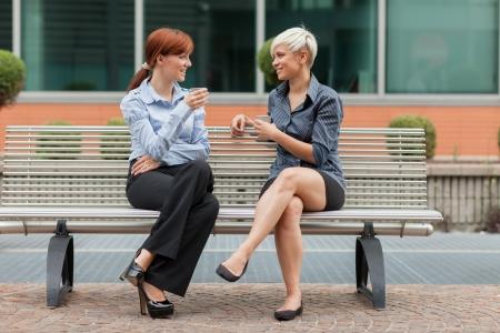 外のベンチに座っていると、話しているビジネスウーマン 写真素材