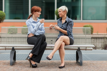 two companies: businesswomen sitting outside on a bench and talking