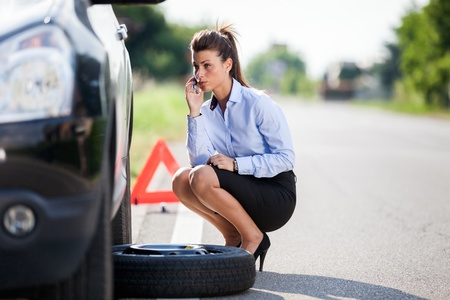 roadside assistance: photo of businesswoman with flat tire