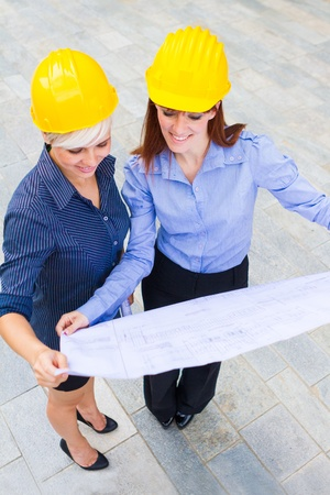 Photo of female constructors holding the project in the hands while smiling Stock Photo - 20669283