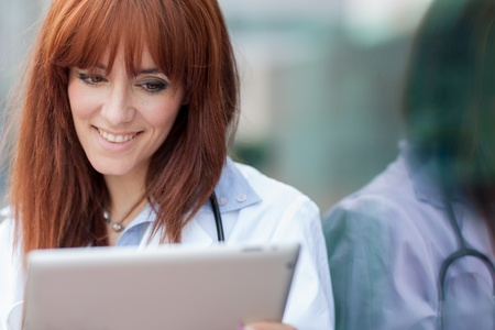 Photo of female doctor with tablet pc standing next to glass wall photo