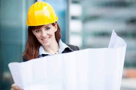 job security: Photo of smiling female constructor with blueprints Stock Photo
