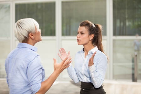 arguments: two businesswoman are arguing on the street