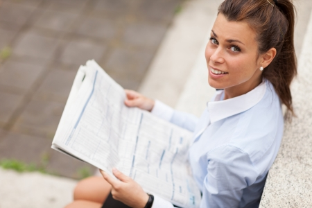photo of brunette businesswoman sitting on stairs with newspaper photo