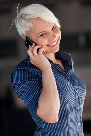 conversating: Photo of Businesswoman who is phoning while smiling