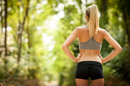 photo of sexy female with tonic bottom looking at running path