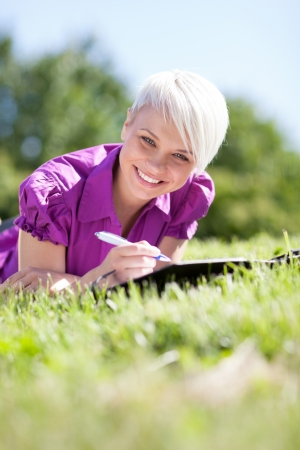 Photo of Beautiful female student is studying in a green field photo