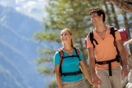 Young couple doing trekking in the mountains while looking around