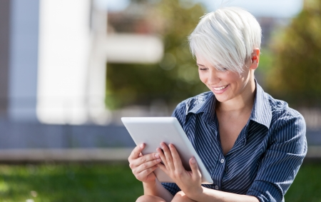 Photo of businesswoman outside in a park with tablet pc photo