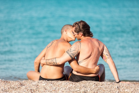 Photo of couple kissing in front of the beach photo