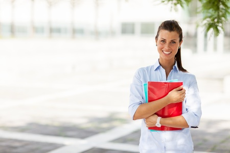 Young attractive female student with notebooks in her hands photo