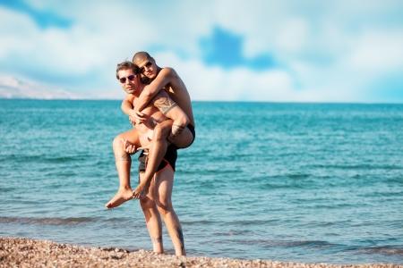 hombres sin camisa: foto de dos hombres enamorados abrazándose unos a otros frente al mar