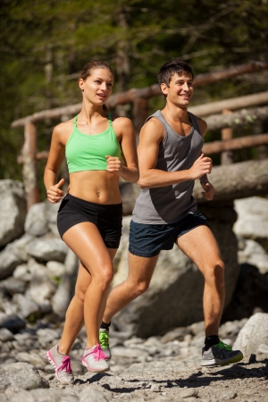 Photo of young sporty couple doing running in the mountains Standard-Bild