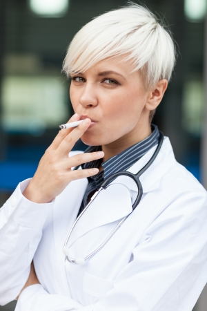 anti tobacco: Conceptual photo of female doctor who is smoking