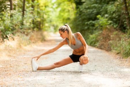 протяжение: Молодая сексуальная женщина блондинка делает упражнения на растяжку Фото со стока