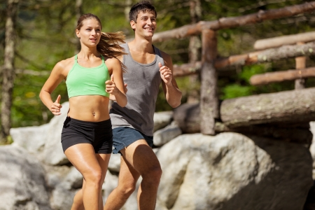 Photo of young sporty couple doing running in the mountains photo