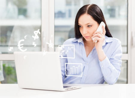 Conceptual image of woman working with phone and computer and trading with her customers photo
