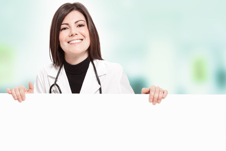 Brunette smiling female doctor with message board photo