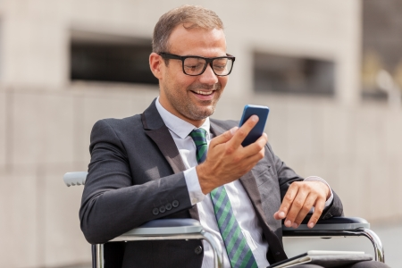 Photo of businessman on wheelchair who is phoning photo