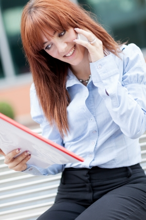 Business image of red hair businesswoman sitting on a metal bench while phoning photo